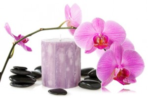 orchid,aromatic candle and black stones on a white background